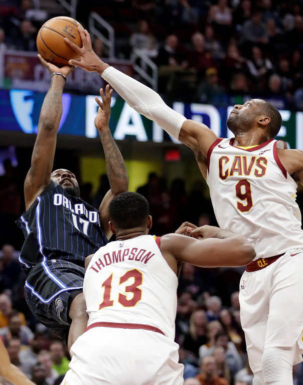 . Cleveland Cavaliers\' Dwyane Wade (9) blocks a shot by Orlando Magic\'s Jonathon Simmons (17) as Tristan Thompson (13) defends during the second half of an NBA basketball game Thursday, Jan. 18, 2018, in Cleveland. The Cavaliers won 104-103. (AP Photo/Tony Dejak)