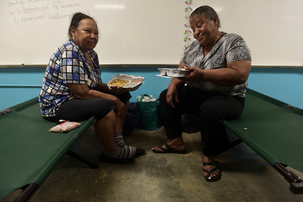 . Modesta, left, and her sister Luz Lopez, from the coastal area Punta Santiago, eat a donated dinner at a makeshift shelter in the Juan Ponce de Leon Elementary School before the arrival of Hurricane Maria, in Humacao, Puerto Rico, Tuesday, Sept. 19, 2017. Puerto Rico is likely to take a direct hit by the category 5 hurricane. Authorities warned people who live in wooden or flimsy homes should find safe shelter before the storm\'s expected arrival on Wednesday. (AP Photo/Carlos Giusti)