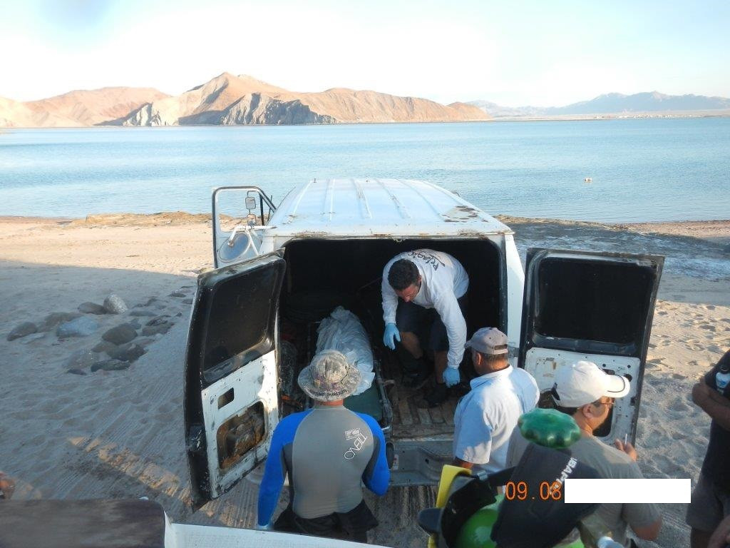 . Joe Jacinto, in the van, helps load his stepfather\'s remains into a San Felipe coroner\'s van on the Gonzaga Bay beach in September, shortly after his team brought the body up from the Erik shipwreck.  (Courtesy of Joe Jacinto)