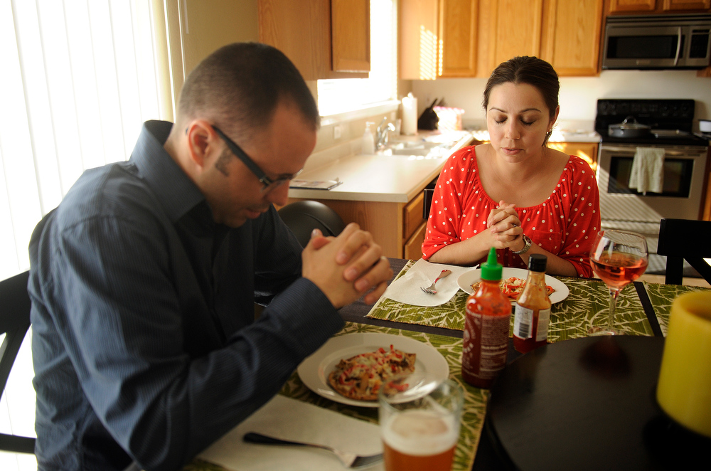 . Bryce and Yanira Owens  say a prayer before eating dinner at their Aurora home on Friday, June 7, 2013. The couple are both from the Alamosa area but did not meet until they were living in Denver. They have been married for 6 years. (Photo By Cyrus McCrimmon/The Denver Post)