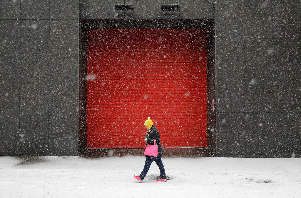 . A woman walks outside of an office building as snow falls, Tuesday, Jan. 21, 2014, in Baltimore.  (AP Photo/Patrick Semansky)