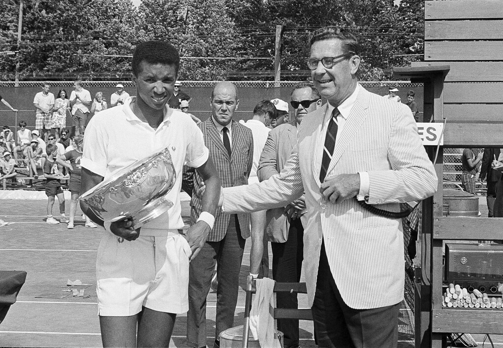 . Tennis star Arthur Ashe Jr., of Richmond, Va., holds the men\'s singles trophy presented by the U.S.L.T.A. after his victory over Marty Rissen of Evanston, Ill., 4-6, 6-3, 6-1, in the National Clay Court tennis tournament in Milwaukee, Wisc., July 24, 1967. Man at right is unidentified.  (AP Photo/Edward Kitch)