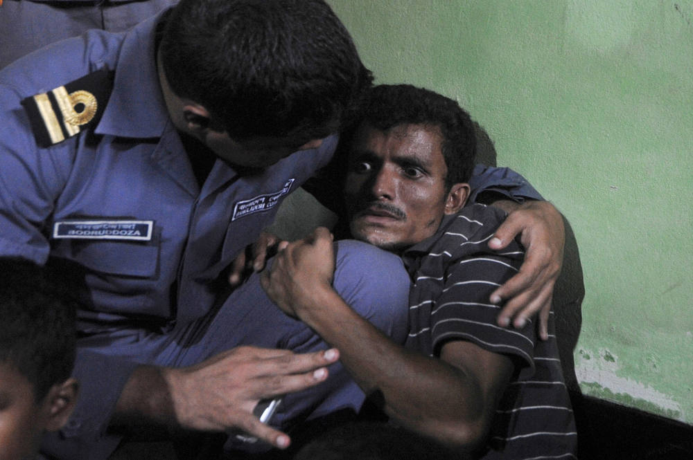 Description of . A Rohingya Muslim from Myanmar (R), who tried to cross the Naf river into Bangladesh to escape sectarian violence, cries  near his family in a Bangladeshi Coast guard station in Teknaf on June 19, 2012, before being sent back to Myanmar. Bangladesh is coming under increasing international pressure to open its border to Rohingya's fleeing the violence, but has so far refused to do so. AFP PHOTO/ Munir uz  ZAMAN/AFP/Getty Images
