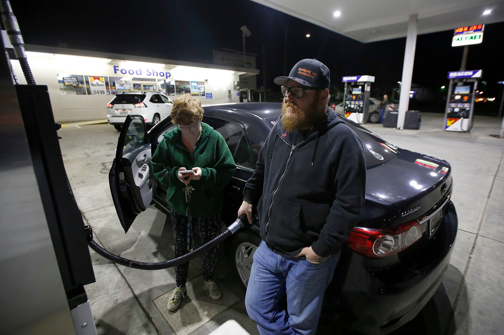 . Chris Mitchell fills his car with gas as his daughter, Austin, checks her mobile phone before evacuating Oroville, Calif., Sunday, Feb. 12, 2017. Mitchell was among the thousands of area residents who left their homes Sunday evening as officials ordered residents near the Oroville Dam in Northern California to evacuate the area after an emergency spillway of the dam severely eroded. (AP Photo/Rich Pedroncelli)