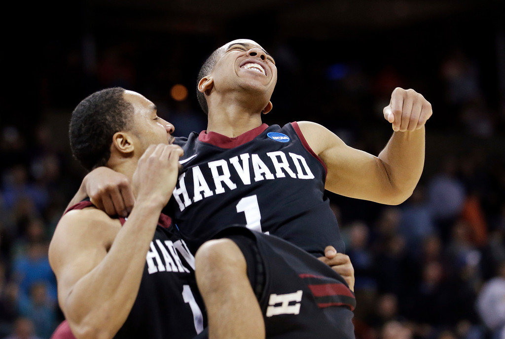 . Harvard\'s Siyani Chambers, right, leaps into the arms of teammate Brandyn Curry after the team beat Cincinnati in the second round of the NCAA college basketball tournament in Spokane, Wash., Thursday, March 20, 2014. Harvard won 61-57. (AP Photo/Elaine Thompson)