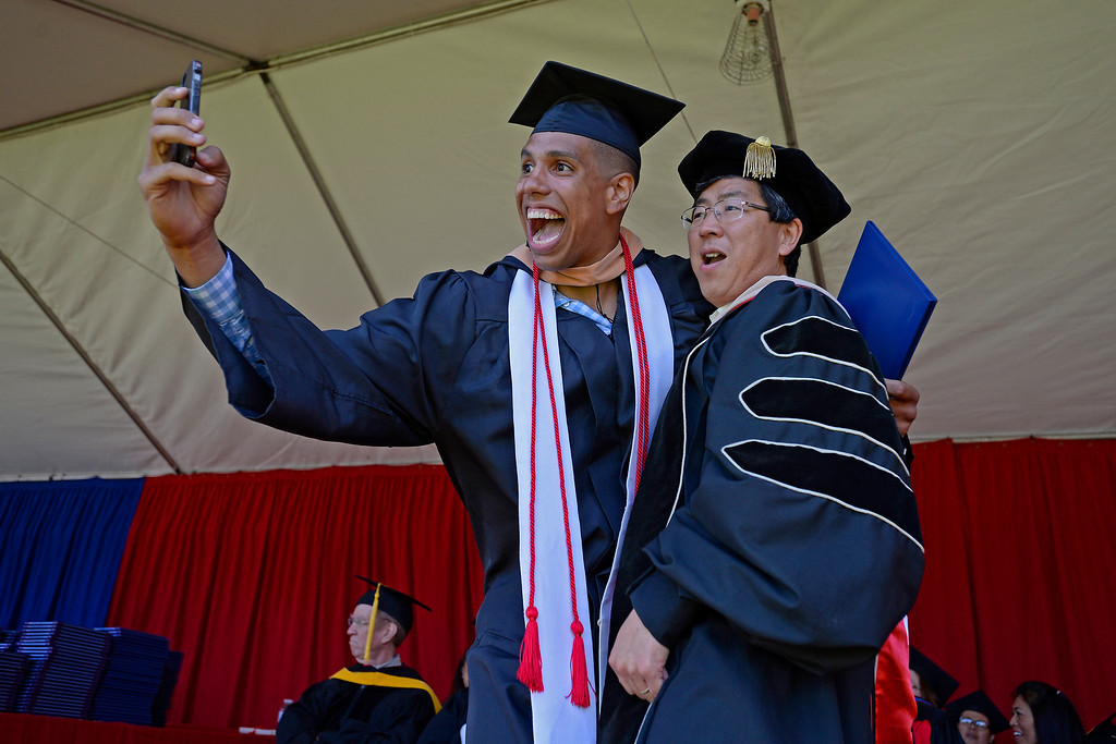 . Bradley Waldow, of Shingle Springs, snaps a selfie with Zhan Li, Saint Mary\'s College dean of the school of economics and business administration after receiving his diploma during the 2014 Saint Mary\'s College commencement ceremony in Moraga, Calif., on Saturday, May 24, 2014. A total of 758 students graduated making this the largest graduating class in school history. (Jose Carlos Fajardo/Bay Area News Group)