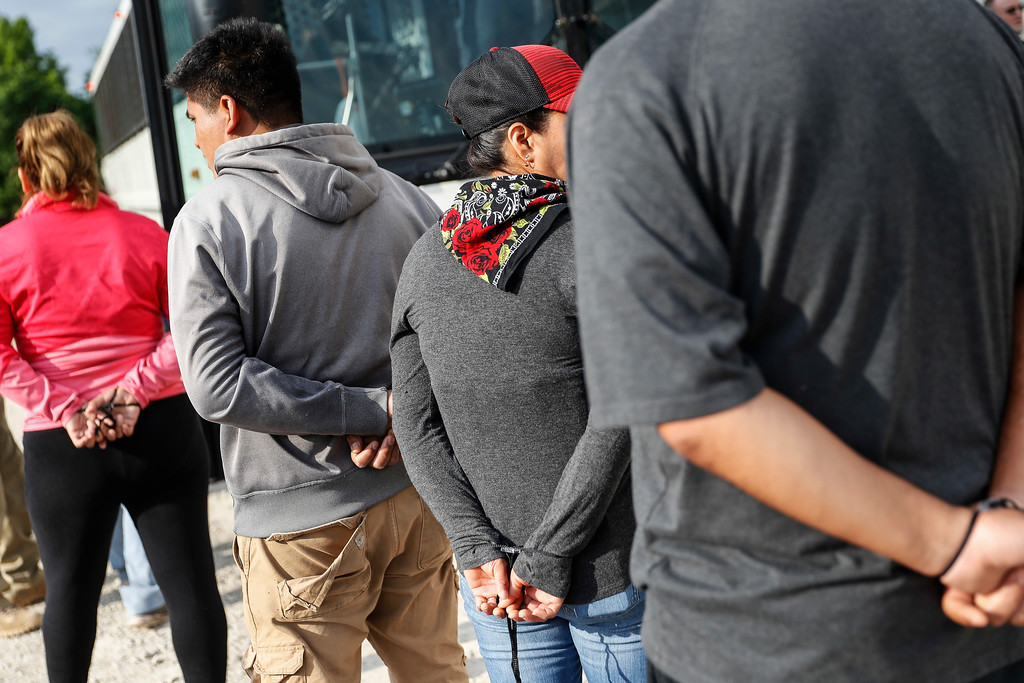 . Suspects wait to be loaded onto a bus during an immigration sting at Corso\'s Flower and Garden Center, Tuesday, June 5, 2018, in Castalia, Ohio. The operation is one of the largest against employers in recent years on allegations of violating immigration laws. (AP Photo/John Minchillo)