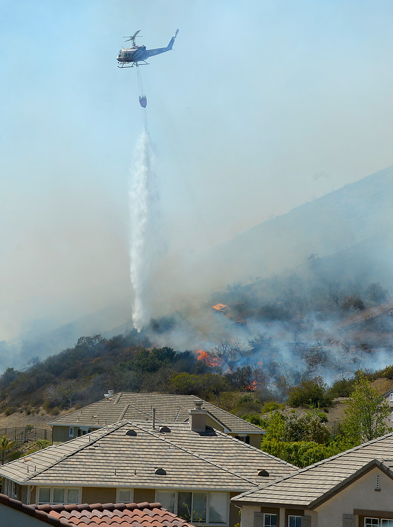 . A helicopter makes a water drop on flames as a wildfire burns along a hillside in Thousand Oaks, Calif., Thursday, May 2, 2013.  (AP Photo/Mark J. Terrill)