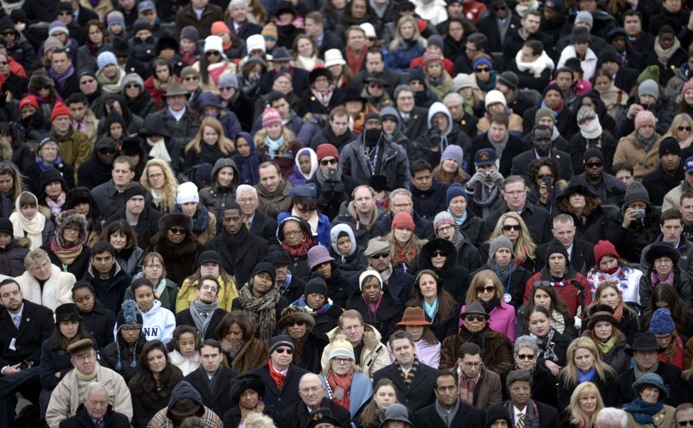 . People listen to US President Barack Obama speak after taking the oath of office during the 57th Presidential Inauguration ceremonial swearing-in at the US Capitol on January 21, 2013 in Washington, DC. The oath was administered by US Supreme Court Chief Justice John Roberts.   BRENDAN SMIALOWSKI/AFP/Getty Images