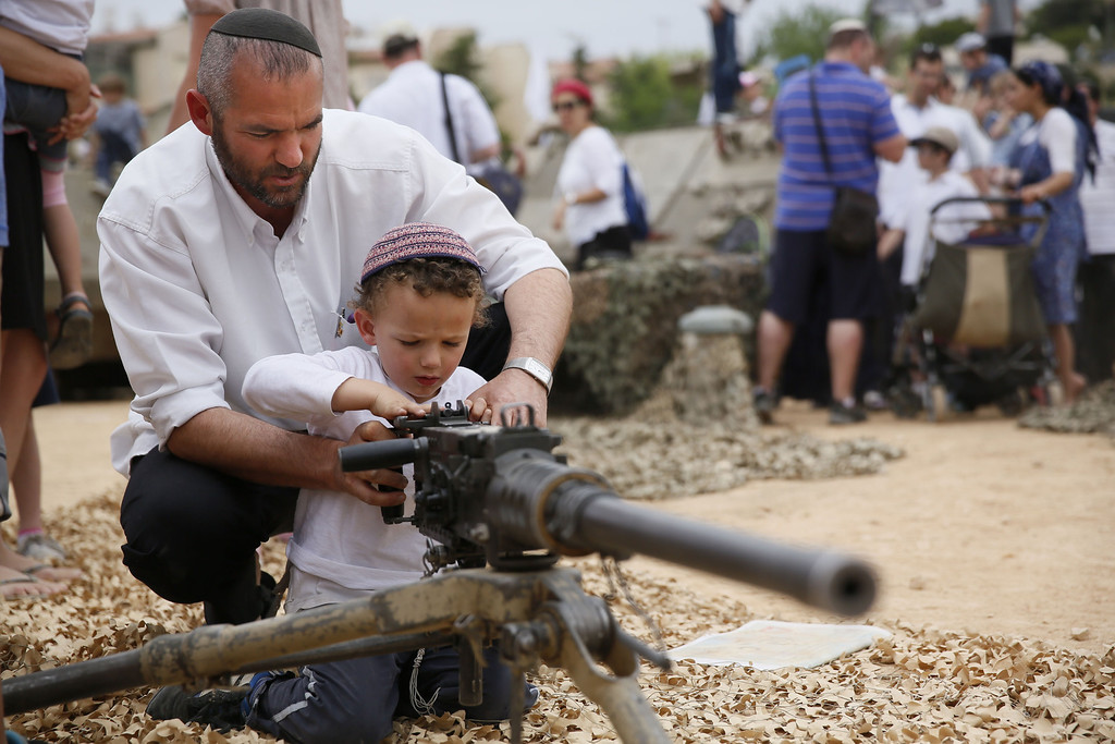 . An Israeli man shows his son how to work a machine gun during a traditional military weapon display to mark the 66th anniversary of Israel\'s Independence at the West Bank settlement of Efrat on May 6, 2014 near the biblical city of Bethlehem. Israelis are marking Independence Day, celebrating the 66th year since the founding of the Jewish State in 1948 according to the Jewish calendar. AFP PHOTO/GALI TIBBON