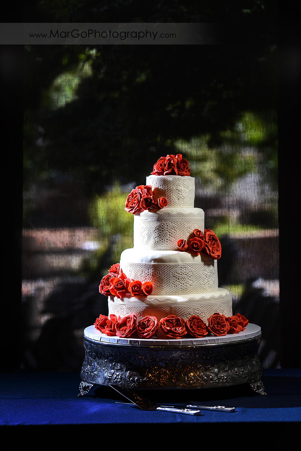 white wedding cake decorated with red flowers at Saratoga Foothill Club