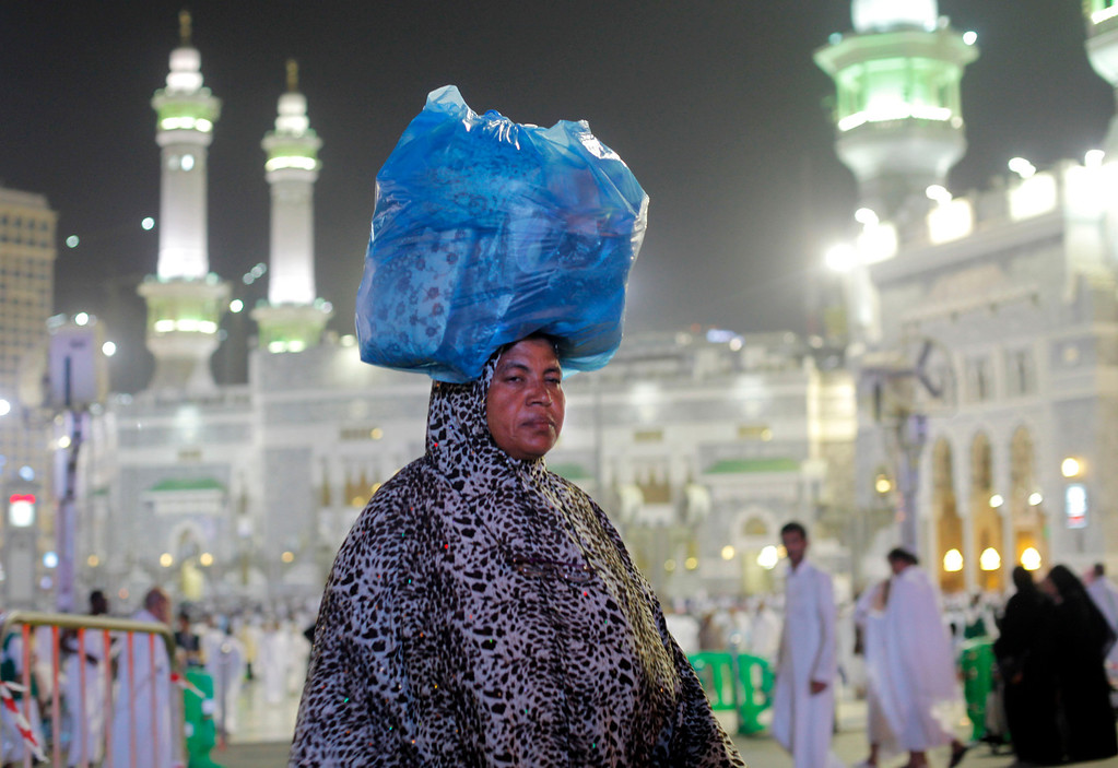. An Muslim pilgrim carries her luggage in front of the Grand Mosque in the holy city of Mecca, Saudi Arabia, late Tuesday, Oct. 8, 2013. The Muslim annual Hajj, or pilgrimage, that will begin on Oct. 14 this year, draws three million visitors each year, making it the largest yearly gathering of people in the world. (AP Photo/Amr Nabil)