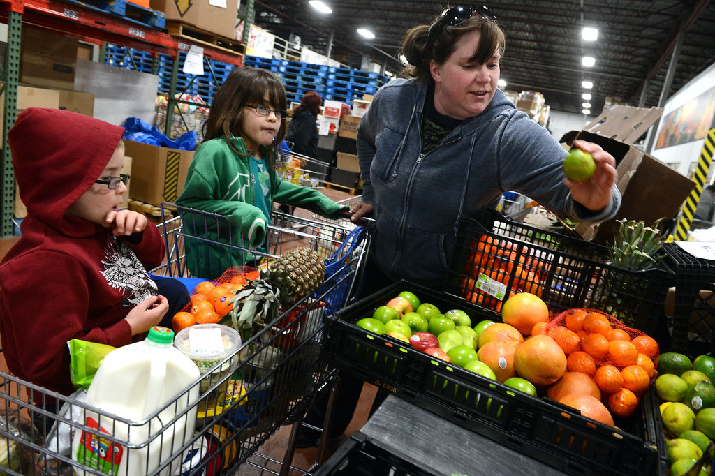 """. Suzanne Hoffman and her children Caitlin, 7, and Alex, 5, right, looks over the produce in the Feeding Families shopping area at the Community Food Share in Longmont, CO, Thursday December 27, 2012. Suzanne said it takes 30 or 40 dollars off her grocery bill, \""""it really helps us out.\""""    Craig F. Walker, The Denver Post"""