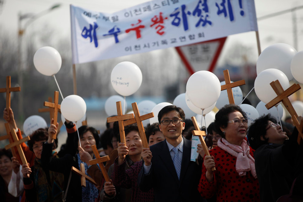 ". South Korean Christians holding crosses take part in a procession to celebrate annual Easter at a church in Icheon, about 80 km (50 miles) southeast of Seoul March 31, 2013. Holy Week is celebrated in many Christian traditions during the week before Easter. The banner reads ""Jesus Christ was resurrected\"".  REUTERS/Kim Hong-Ji"