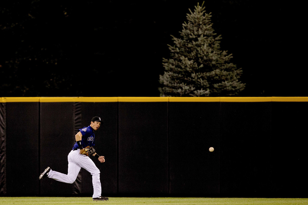. DENVER, CO - JULY 2:  Center fielder Tyler Colvin #21 of the Colorado Rockies tracks down a double off the bat of Hanley Ramirez of the Los Angeles Dodgers  during the ninth inning at Coors Field on July 2, 2013 in Denver, Colorado.  The Dodgers defeated the Rockies 8-0. (Photo by Justin Edmonds/Getty Images)