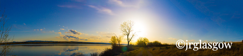 Panorama of the sun setting behind a tree on the edge of a lake.
