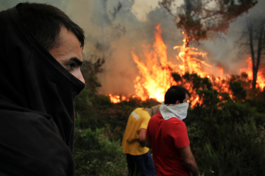. Inhabitants covering their faces with cloths watch a wildfire near Caramulo, north Portugal, Thursday, Aug. 29, 2013.  (AP Photo/Francisco Seco)