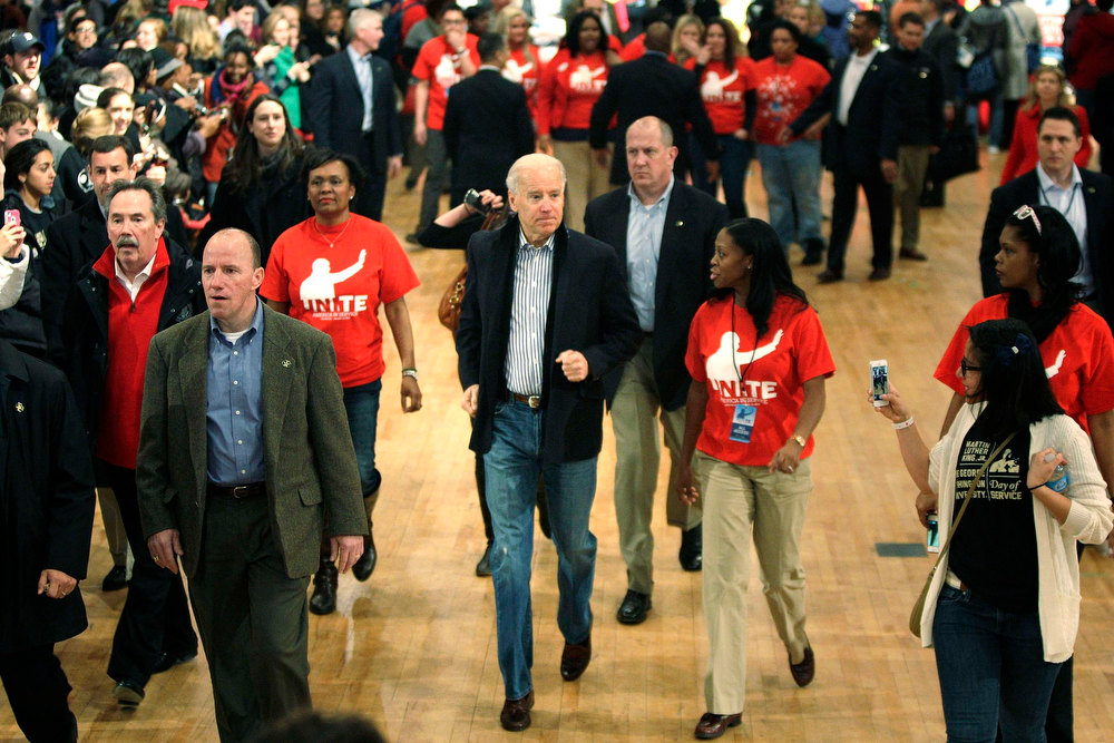 . U.S. Vice President Joe Biden (C) jogs to the stage for remarks after helping assemble care kits for U.S. military service members and veterans at a Unite America in Service event at the National Guard Armory in Washington, January 19, 2013. Biden and his family volunteered for the event during the National Day of Service as part of the 57th Presidential Inauguration. REUTERS/Jonathan Ernst