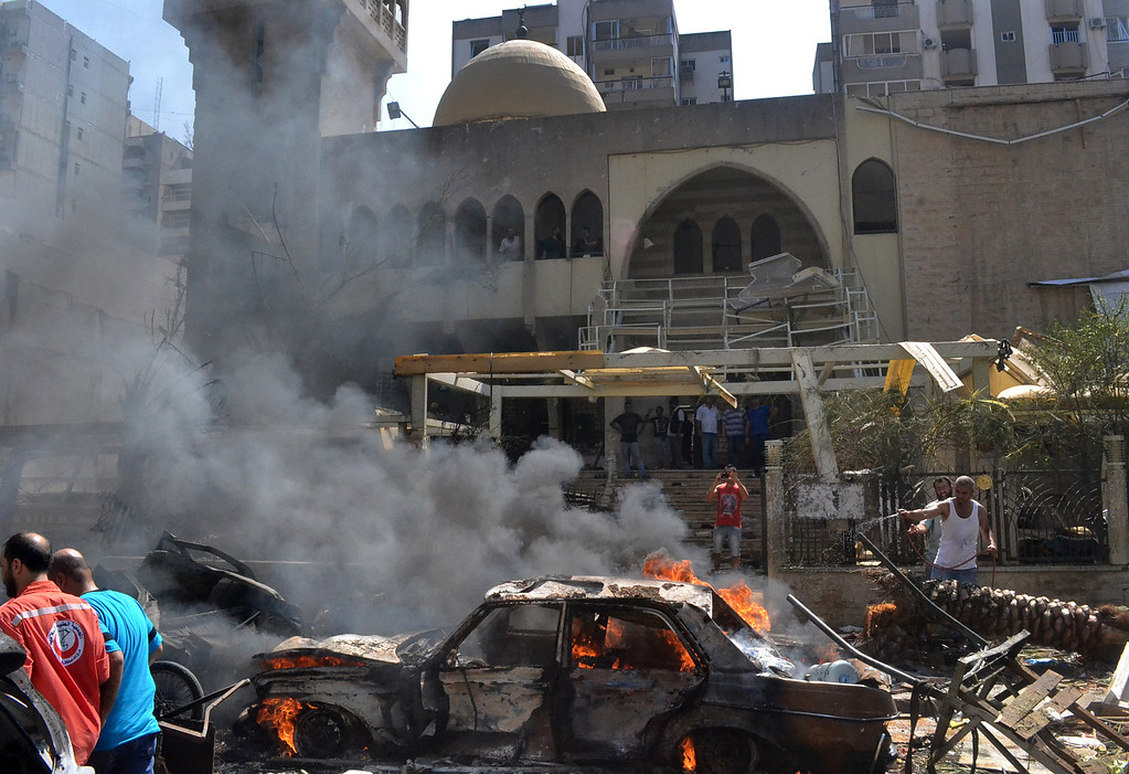 . A burning car is seen at the entrance of a mosque which was attacked by a car bomb, in the northern city of Tripoli, Lebanon, Friday, Aug. 23, 2013. (AP Photo)