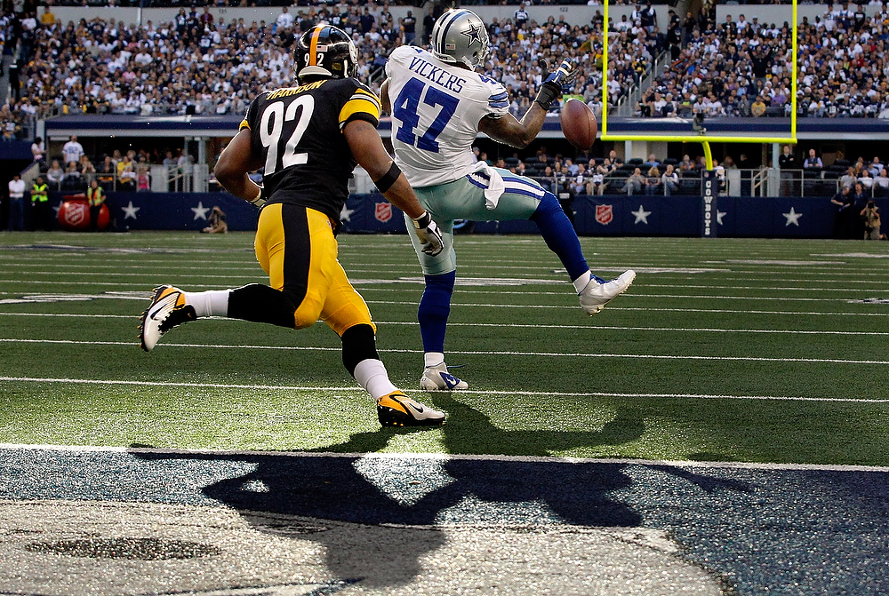Description of . Lawrence Vickers #47 of the Dallas Cowboys bobbles a pass incomplete against James Harrison #92 of the Pittsburgh Steelers at Cowboys Stadium on December 16, 2012 in Arlington, Texas.  (Photo by Tom Pennington/Getty Images)