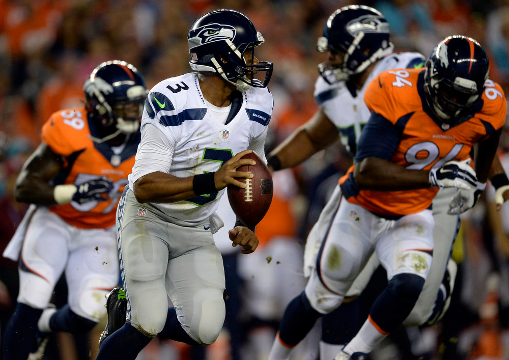 . Quarterback Russell Wilson (3) of the Seattle Seahawks gets flushed out of the pocket by outside linebacker Danny Trevathan (59) of the Denver Broncos and defensive end DeMarcus Ware (94) of the Denver Broncos during the first half.  The Denver Broncos vs the Seattle Seahawks At Sports Authority Field at Mile High. (Photo by AAron Ontiveroz/The Denver Post)