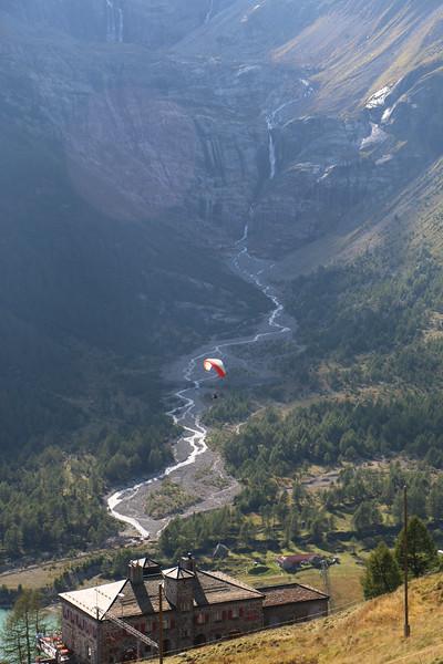 View of paraglider over Alp Grum railway station from Albergo Belvedere