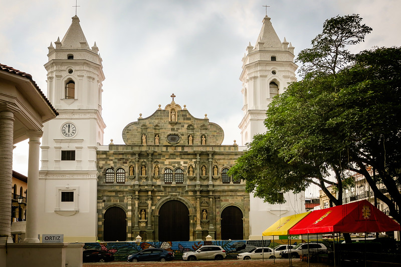 The spires of an old town church near a tree-shaded square in Panama City