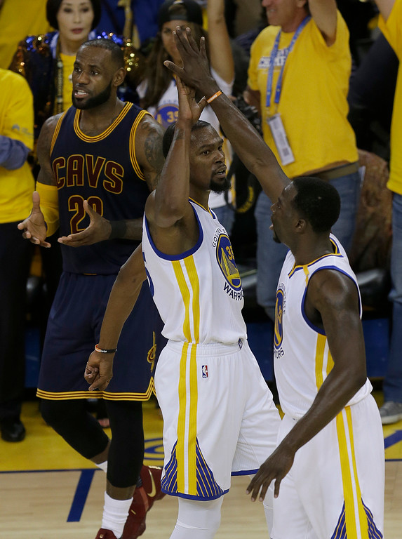 . Golden State Warriors forward Kevin Durant, center, reacts with forward Draymond Green in front of Cleveland Cavaliers forward LeBron James, top left, during the first half of Game 1 of basketball\'s NBA Finals in Oakland, Calif., Thursday, June 1, 2017. (AP Photo/Ben Margot)