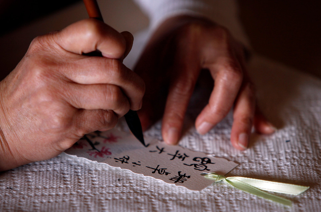 """. A calligrapher makes personalized cards for visitors at Hakone Estate and Gardens which hosted a Lunar New Year of the Snake festival with a \""""Chinese Village Fair\"""" on Sunday afternoon, March 3, 2013 in Saratoga, Calif. (Karl Mondon/Staff)"""