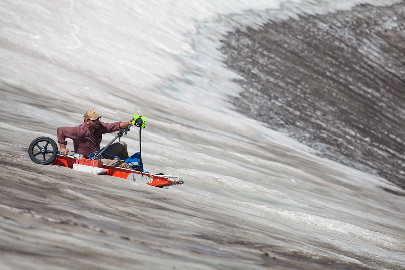 A USGS researcher sleds down a steep alpine icepatch with a ground penetrating radar and mapping prism in order to map the surface and interior of the ice