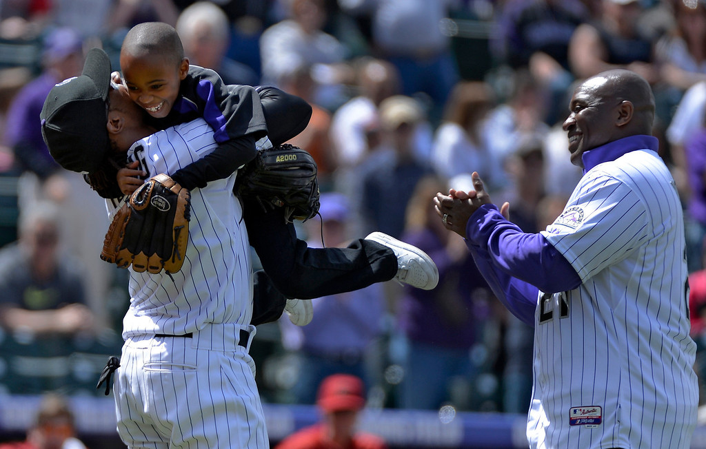 . DENVER, CO. - APRIL 21: Colorado Rockies retired player Eric Young (R) looks on as stands Dallas Young 6-years-old jumps in the arms of his older brother Eric Young Jr. after throwing out the first pitch prior to their game against the Arizona DiamondBacks April 21, 2013 at Coors Field. (Photo By John Leyba/The Denver Post)