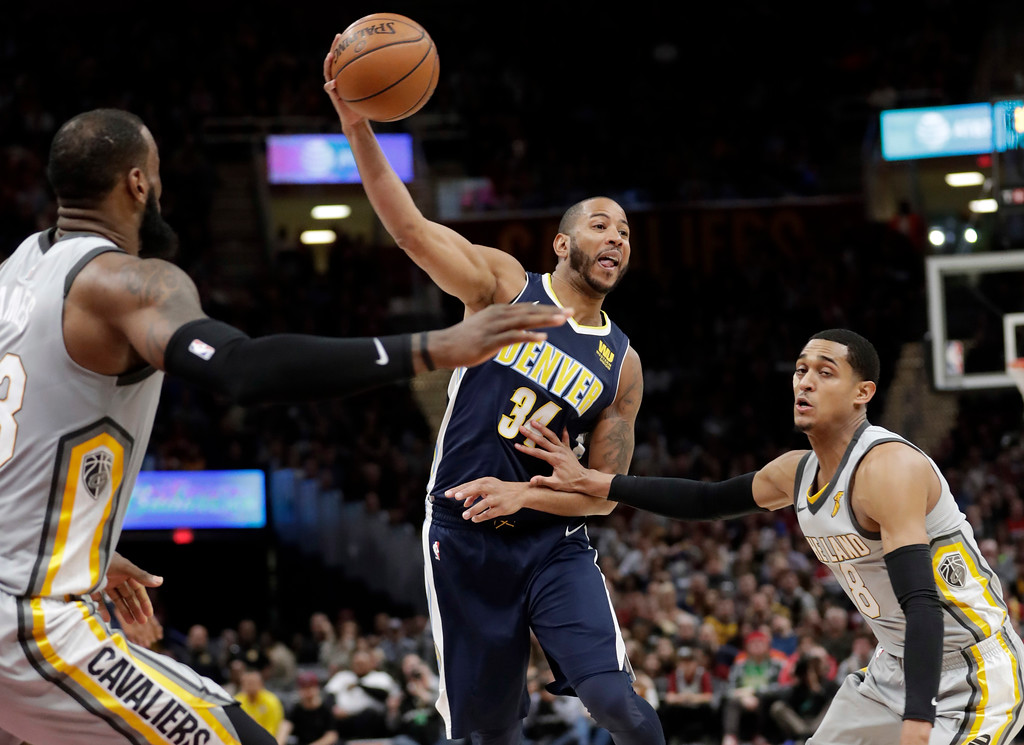 . Denver Nuggets\' Devin Harris (34) passes against Cleveland Cavaliers\' LeBron James (23) and Jordan Clarkson in the second half of an NBA basketball game, Saturday, March 3, 2018, in Cleveland. The Nuggets won 126-117. (AP Photo/Tony Dejak)