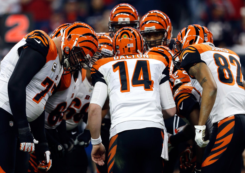 Description of . Andy Dalton #14 of the Cincinnati Bengals stands in the huddel with teammates against the Houston Texans during their AFC Wild Card Playoff Game at Reliant Stadium on January 5, 2013 in Houston, Texas.  (Photo by Scott Halleran/Getty Images)