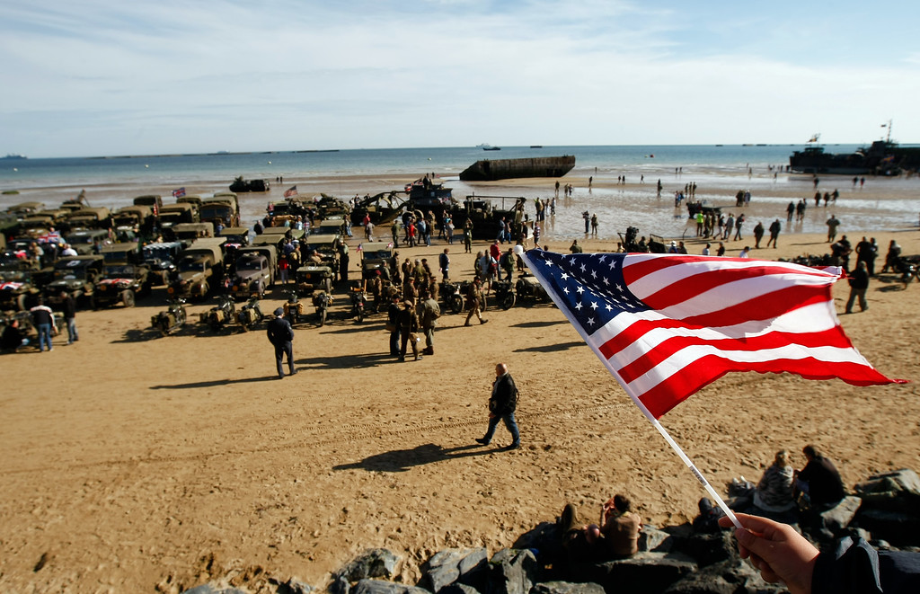 . An onlooker waves an American flag as World War II military vehicles are displayed on the beach of Arromanches, France, Friday, June 6, 2014, as part of D-Day commemorations. World leaders and veterans gathered by the beaches of Normandy, northern France, on Friday to mark the 70th anniversary of the World War II D-Day landings. (AP Photo/Claude Paris)