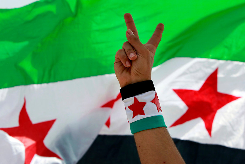 . A Syrian activist flashes the victory sign during a protest against the participation of Hezbollah in the Syrian war, at Martyrs square in Beirut, Lebanon, Sunday, June 9, 2013. A senior Lebanese military official says clashes have erupted outside the Iranian embassy in the capital between protesters opposing Hezbollah\'s participation in the Syrian war and unidentified locals, killing one demonstrator. The Syrian revolutionary flag is seen at background. (AP Photo/Bilal Hussein)