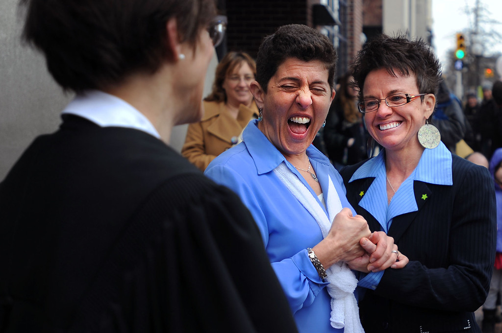 . Lisa Ruby and Lisa Cavico celebrate as they get married after 8 years together outside the Washtenaw County Clerk\'s office in Ann Arbor, Mich., Saturday, March 22, 2014, the day after a federal court struck down Michigan\'s ban on gay marriage. (AP Photo/The Ann Arbor News, Brianne Bowen)