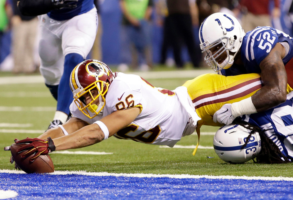 . Washington Redskins tight end Jordan Reed reaches in to the end zone as he\'s stopped by Indianapolis Colts inside linebacker D\'Qwell Jackson, top, and free safety Sergio Brown during the second half of an NFL football game Sunday, Nov. 30, 2014, in Indianapolis. Reed was called down short of the end zone.  (AP Photo/AJ Mast)