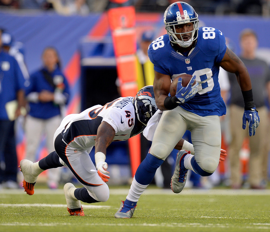 . New York Giants wide receiver Hakeem Nicks (88) picks up a few yards and is caught by Denver Broncos cornerback Dominique Rodgers-Cromartie (45) during the second quarter September 15, 2013 MetLife Stadium. (Photo by John Leyba/The Denver Post)