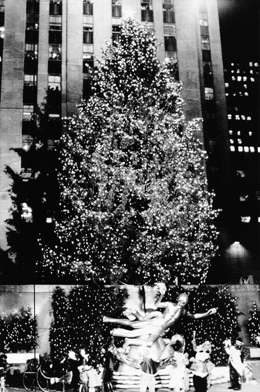 . The Christmas tree at New York\'s Rockefeller Center stands lit, ablaze with multi-colored lights, Dec. 9, 1985. Thousands of children and adults crowded Rockefeller Center to watch the annual lighting of the tree. Beneath the tree is the famed statue of Prometheus. (AP Photo/G. Paul Burnett)