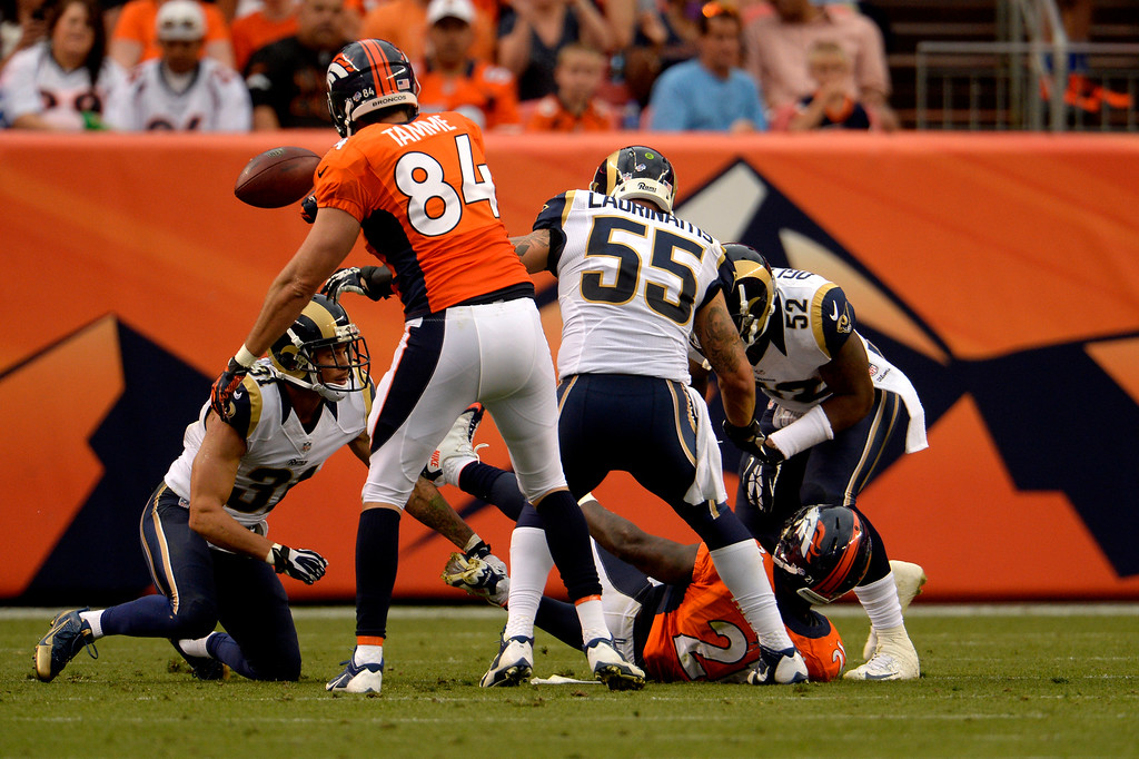 . DENVER, CO. - August 24: linebacker Alec Ogletree (52) of the St. Louis Rams rips the ball from running back Ronnie Hillman (21) of the Denver Broncos in the first half during the 3rd pre-season game of the season at Sports Authority Field at Mile High. August 24, 2013 Denver, Colorado. (Photo By Joe Amon/The Denver Post)