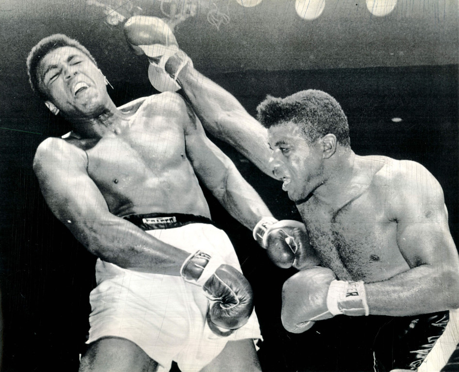 . Floyd Patterson shoots a straight right but champion Cassius Clay ducks back and takes blow on shoulder in their heavyweight title fight at Las Vegas.  Clay got in almost all effective punches to win by a TKO in the 12th round.  1965. Credit: AP