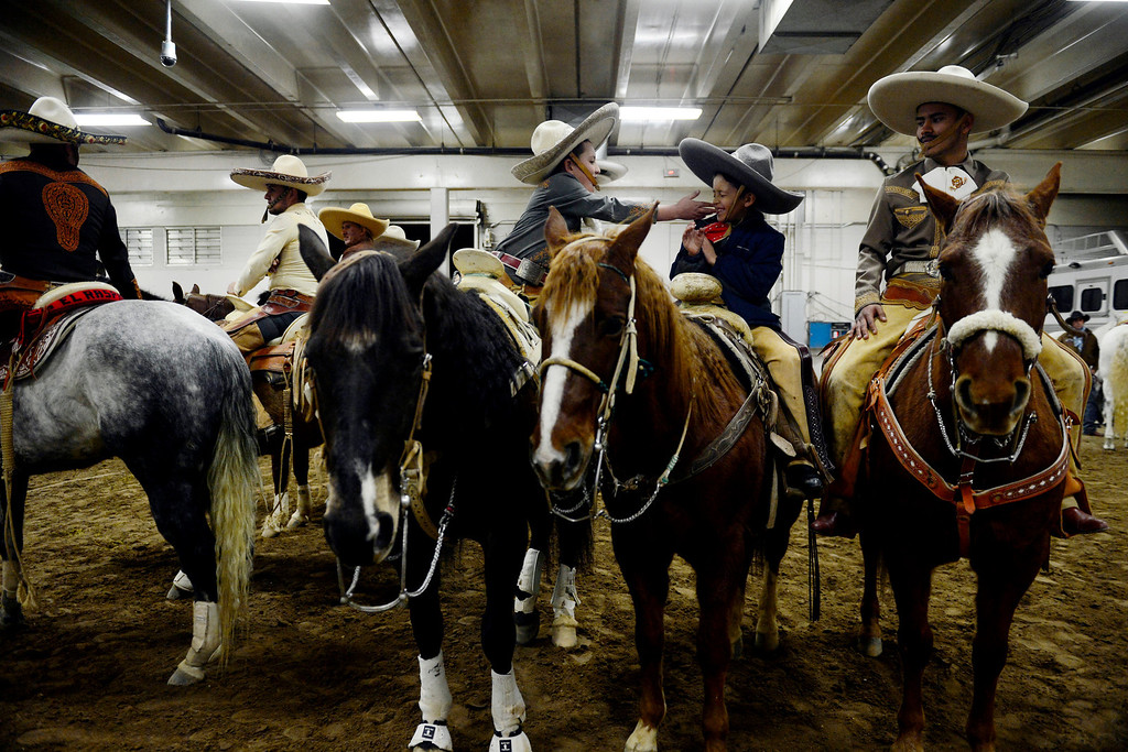 . Ricardo Madera, 11, goofs around with his his cousin Luis Madera, 8, as they sit atop their horses during National Western Stock Show\'s Mexican Rodeo Extravaganza at the Denver Coliseum on Sunday, Jan. 13, 2013. AAron Ontiveroz, The Denver Post