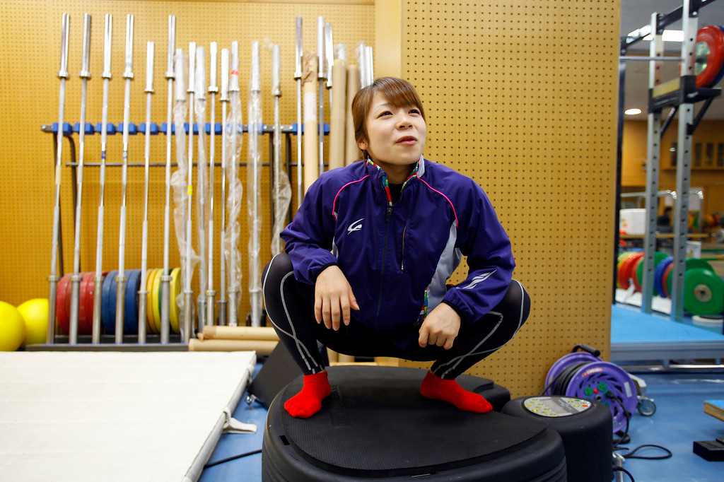. In this Friday, Aug. 30, 2013 photo, Japanese weightlifter Hiromi Miyake, silver medalist in the London Olympic women\'s 48kg event, squats on a machine to warm up for muscle and body balance before her training at one of Tokyo\'s leading training centers. The Olympics are in Miyake\'s blood, a heritage that stretches back to the 1960s, when her uncle won a gold medal at the 1964 Tokyo Games and her father won bronze in Mexico City in 1968. With the Olympics coming to Tokyo in 2020, she hopes that will inspire the next generation of Japanese athletes. (AP Photo/Junji Kurokawa)