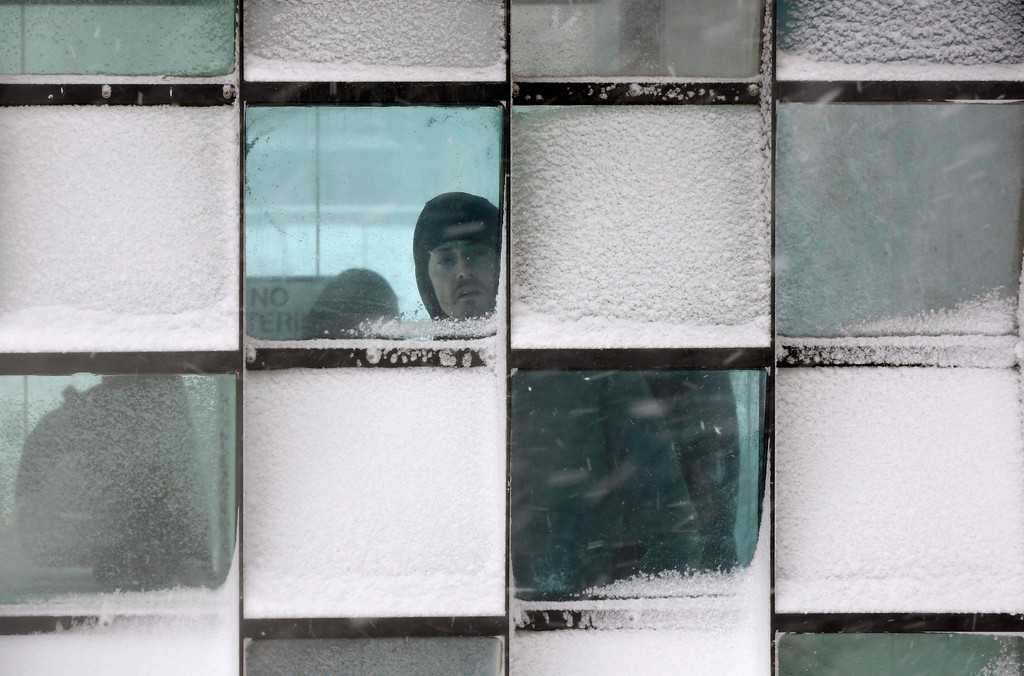 . A man peers out from a from a bus stop during a winter storm, Tuesday, March 13, 2018, in Portland, Maine. The third major nor\'easter in two weeks slammed the storm-battered Northeast Tuesday with blizzard conditions. (AP Photo/Robert F. Bukaty)