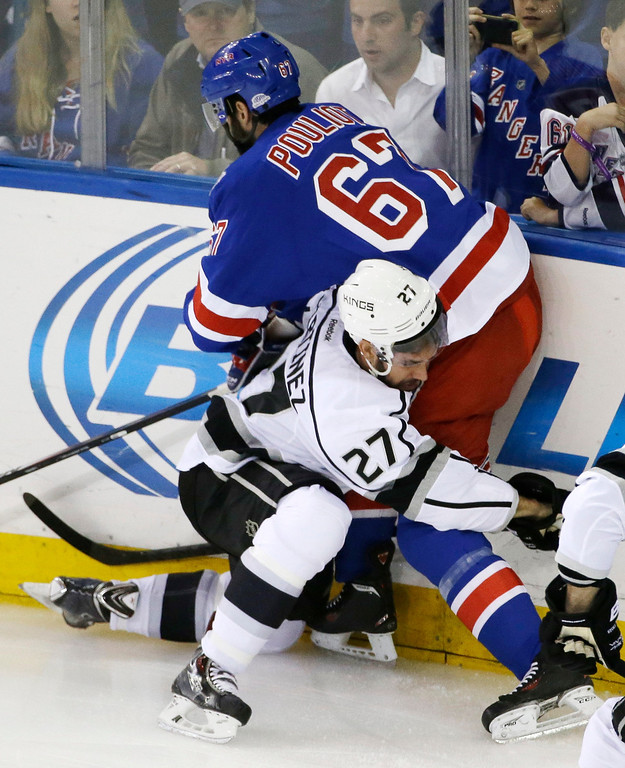 . New York Rangers left wing Benoit Pouliot (67) collides with Los Angeles Kings defenseman Alec Martinez (27) in the first period during Game 3 of the NHL hockey Stanley Cup Final, Monday, June 9, 2014, in New York. (AP Photo/Frank Franklin II)