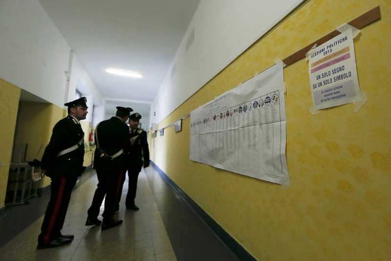 ". Italian Carabinieri police stand in front of an electoral poster and a banner (R) that reads ""One sign on one symbol\"" in a polling station in Rome February 24, 2013. Italians began voting on Sunday in one of the most closely watched elections in years, with markets nervous about whether it can produce a strong government to pull Italy out of recession and help resolve the euro zone debt crisis. REUTERS/Yara Nardi"