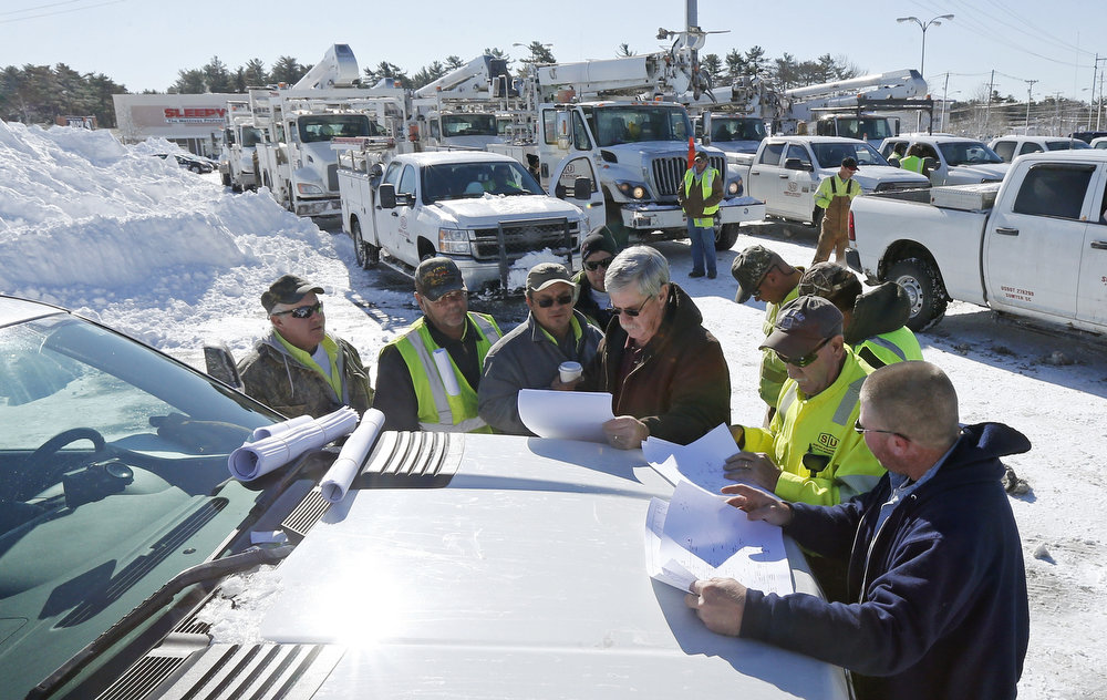 . With more than a hundred trucks waiting to deploy, National Grid and utility workers from South Carolina meet on the hood of a pick-up truck to discuss their plan to re-energize towns without power at the Hanover Mall in Hanover, Mass., Sunday, Feb. 10, 2013.  A howling storm across the Northeast left the New York-to-Boston corridor shrouded in 1 to 3 feet of snow Saturday, stranding motorists on highways overnight and piling up drifts so high that some homeowners couldn\'t get their doors open. More than 650,000 homes and businesses were left without electricity. (AP Photo/Charles Krupa)