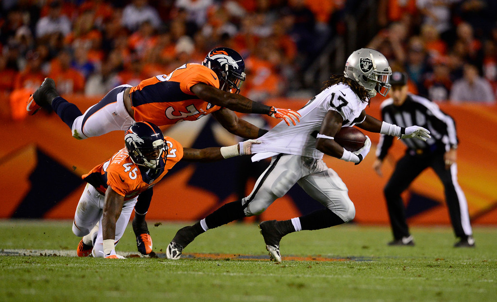 . DENVER, CO - SEPTEMBER 23: Oakland Raiders wide receiver Denarius Moore (17) breaks a tackle by Denver Broncos cornerback Dominique Rodgers-Cromartie (45) and Denver Broncos strong safety Duke Ihenacho (33) and scores a touchdown in the second quarter. The Denver Broncos took on the Oakland Raiders at Sports Authority Field at Mile High in Denver on September 23, 2013. (Photo by AAron Ontiveroz/The Denver Post)