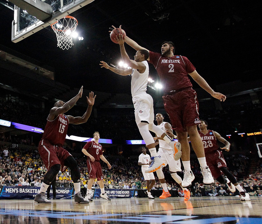 . San Diego State�s Aqeel Quinn, center, shoots against New Mexico State�s Sim Bhullar (2) during the first half of a second-round game of the NCAA men\'s college basketball tournament in Spokane, Wash., Thursday, March 20, 2014. (AP Photo/Young Kwak)