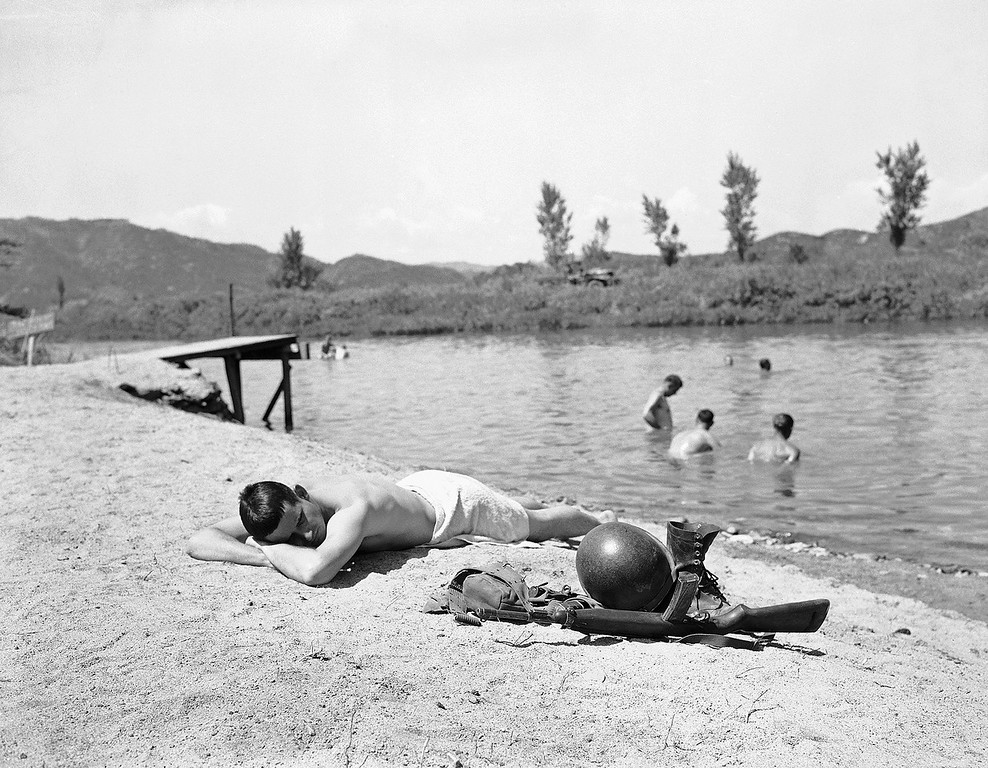 . With clothes, helmet and rifle at his side, Sgt. Harry Heldreth of 1387 Lake View Road, Cleveland, Ohio, sunbathes on an Imjin River beach in Korea not far behind the front lines, July 4, 1951. (AP Photo/William Straeter)